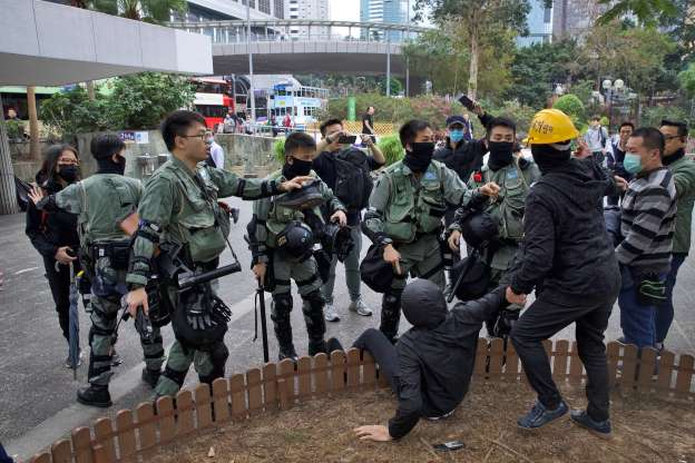 Riot police chase and corner a masked man who fell as another man tries to assist him ahead of a rally demanding electoral democracy and call for boycott of the Chinese Communist Party and all businesses seen to support it in Hong Kong, Sunday, Jan. 19, 2020. Hong Kong has been wracked by often violent anti-government protests since June, although they have diminished considerably in scale following a landslide win by opposition candidates in races for district councilors late last year. (AP Photo/Ng Han Guan)