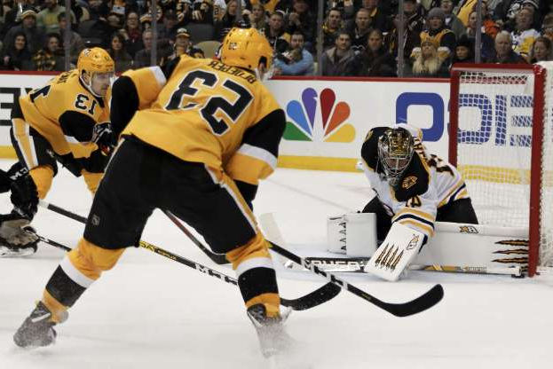 a hockey player standing in the snow: Bruins goalie Jaroslav Halak was able to stop this Penguins bid in the second period as Teddy Blueger looked for a rebound chance.