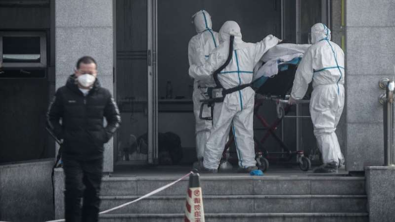 a man standing next to a building: Medical staff carry a patient with the new coronavirus into Wuhan's Jinyintan hospital