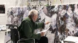 a man that is standing in the snow: Gordon Smith works on one his works for his exhibition Black Paintings about his time as an Intelligence Officer in World War II.