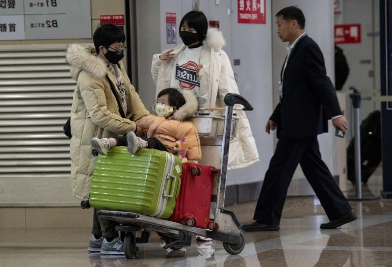a group of people standing around a bag of luggage: Travellers wearing protective masks arrive at the Beijing Capital Airport in Beijing.