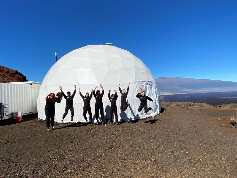 a group of people standing outside of a building: The Sensoria crew jumps for joy before entering the mock Martian habitat on Jan. 4, 2020. The crew will stay in the habitat until Jan. 18, 2020.
