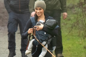 Her Royal Happiness: Meghan Markle beams as she takes her dogs for a walk with Archie in a baby carrier - as Prince Harry finally arrives in Canada to start their new life after his last royal engagement