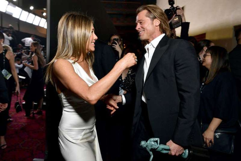 a group of people standing next to a person in a suit and tie: Brad Pitt and Jennifer Aniston backstage at the 2020 SAG Awards | Emma McIntyre/Getty