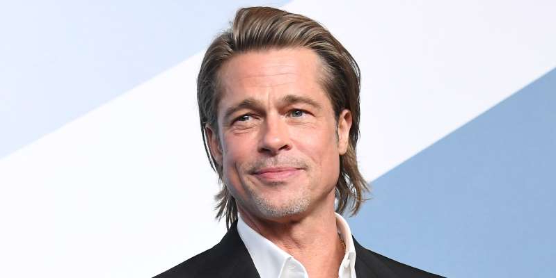 a man wearing a suit and tie smiling at the camera: Forget ex-wives, and LDC, and heartwarming speeches built for Twitter: here's how to get Brad Pitt's wonderful, enviable hair.