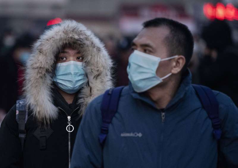 a person standing in front of a crowd: Chinese travellers wear protective masks as they arrive to board trains at Beijing Railway on January 21, 2020 in Beijing, China. The number of cases of a new coronavirus has risen to nearly 300 in mainland China. Beijing is among cities affected.