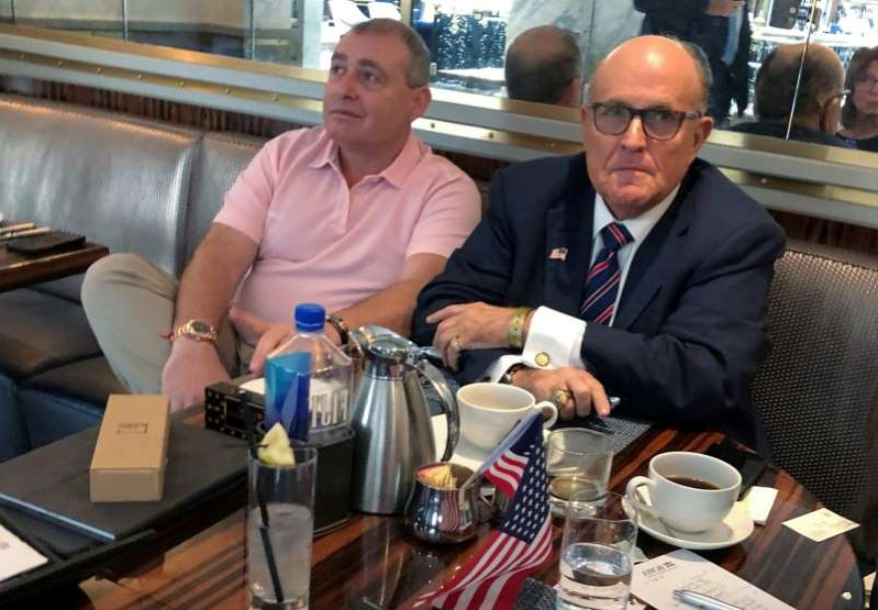Rudy Giuliani et al. sitting at a table: FILE PHOTO: U.S. President Trump's lawyer Rudy Giuliani has coffee with Russian born businessman Parnas at Trump Hotel in Washington