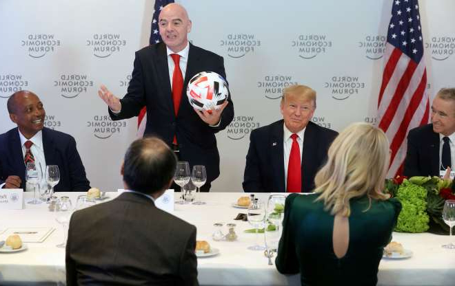 Slide 1 of 27: U.S. President Donald Trump listens to FIFA President Gianni Infantino speak during a dinner with global CEOs during the 50th World Economic Forum (WEF) annual meeting in Davos, Switzerland, January 21, 2020.