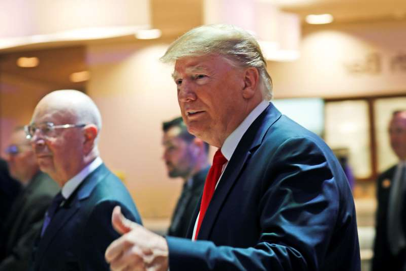 U.S. President Donald Trump flashes a thumbs-up as he arrives at the World Economic Forum in Davos, Switzerland, Wednesday, Jan. 22, 2020. The 50th annual meeting of the forum is taking place in Davos from Jan. 21 until Jan. 24, 2020. Right is Executive Chairman Klaus Schwab.