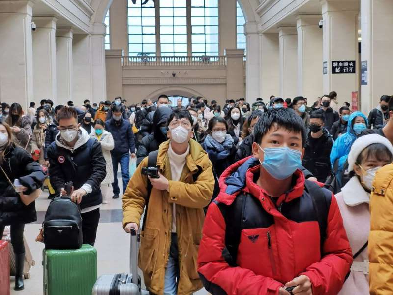 a group of people standing in front of a crowd: Commuters wear face masks as they wait at a train station in Wuhan, China.