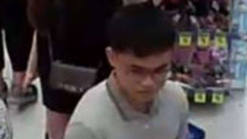 a man looking at the camera: Police say the man followed a woman down an aisle before sexually assaulting her.