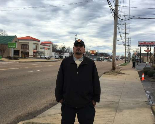 a man that is standing in the street: Lazaro Ponce stands on Summer Avenue, where he looks for work as a day laborer in Memphis, Tennessee. Ponce claims to be the mystery man who helped a baby in the El Paso Walmart shooting on Aug. 3, 2019.