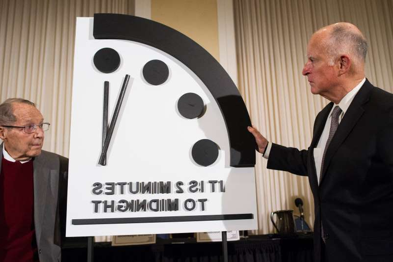 a man wearing a suit and tie: Former California Gov. Jerry Brown, left, and former Secretary of Defense William Perry unveil the Doomsday Clock during the Bulletin of the Atomic Scientists news conference in Washington, Thursday, Jan. 24, 2019.  The Doomsday Clock is set at two minutes to midnight.