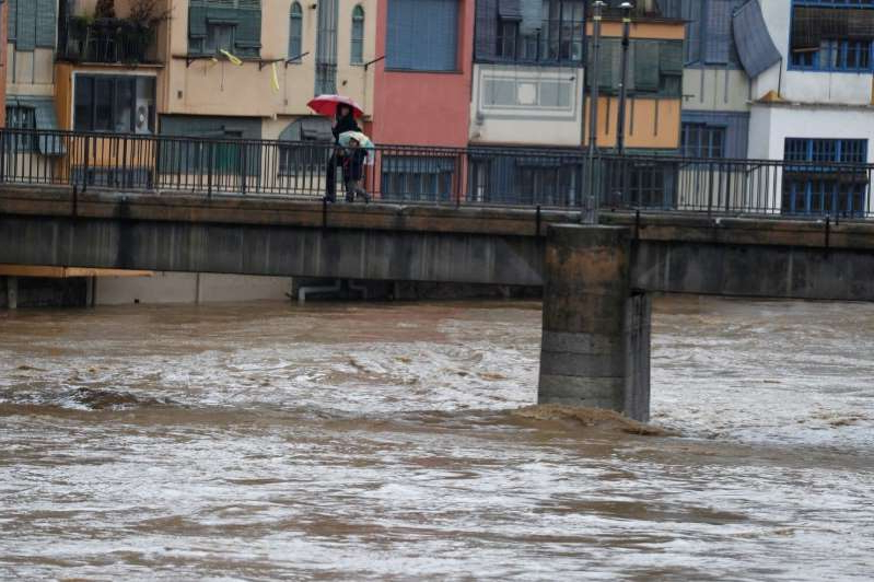 a bridge over a body of water: Residents walk on a bridge on the Onyar river during the storm