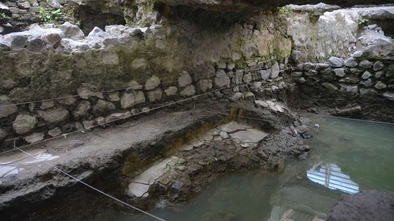 a large waterfall next to a rock wall: Remains of the steambath found beneath Mexico City. (Image: INAH)