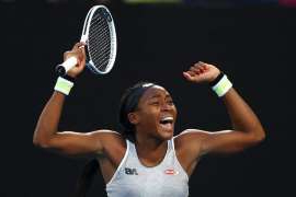 a woman holding a racket on a court: Coco Gauff celebrates her win over defending champion Naomi Osaka at the Australian Open.
