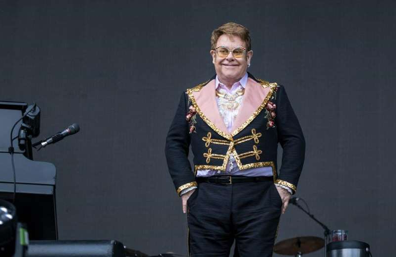 Elton John wearing a suit and tie: Sir Elton John