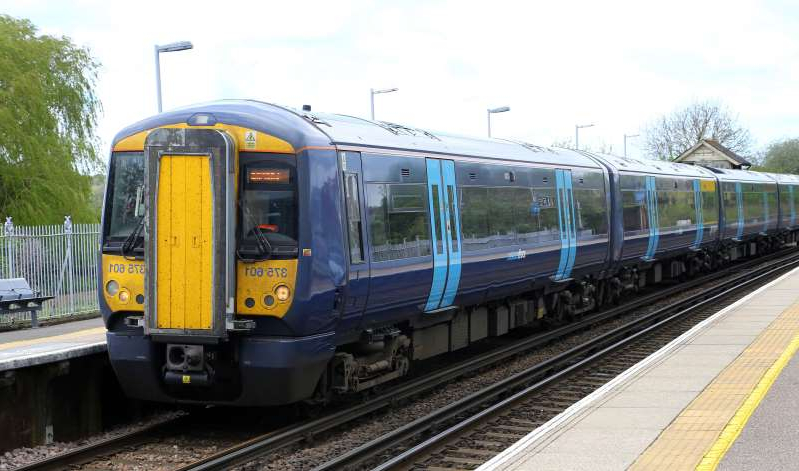 a blue and yellow train pulling into a station: A Southeastern train passes through Wye in Kent. Picture date: Friday April 26, 2019. Photo credit should read: Gareth Fuller/PA Wire