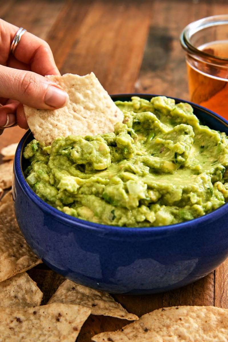 a hand holding a bowl of food: Best Guacamole