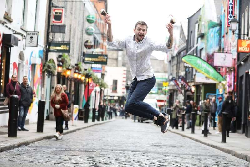 a man doing a trick on a skateboard on a sidewalk: Overall winner Rory Mc Gee from The Shelbourne in Cork jumps for joy on International Coffee Day in the Old Storehouse Temple Bar where a Guinness World Record attempt was  made in Dublin for the most Irish coffees prepared in under three minutes