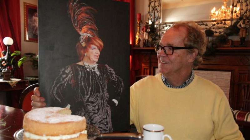 a man sitting at a table in front of a cake: Tommy Jeffs and his drag character, Tallulah, have hosted many charity events raising millions over the past five decades. (ABC Central West: Kathleen Ferguson)