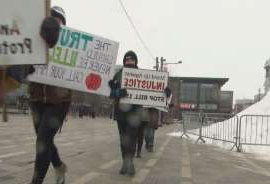 a group of people walking down a street next to a sign: Ottawa animal rights activists protested Saturday at Lansdowne Park.