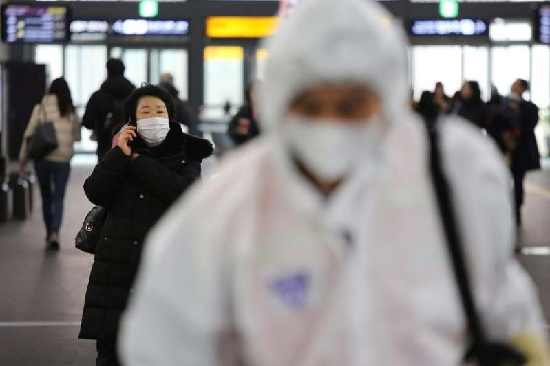 a person standing in front of a crowd: A woman wears a mask as an employee works to prevent a new coronavirus at Suseo Station in Seoul, South Korea, Friday, Jan. 24, 2020.