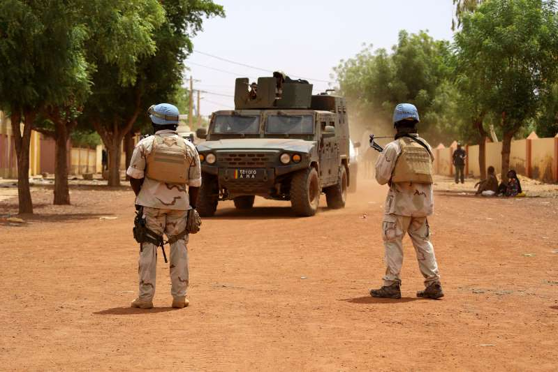 Senegalese soldiers of the UN peacekeeping mission in Mali MINUSMA (United Nations Multidimensional Integrated Stabilisation Mission in Mali) patrol in the streets of Gao, on July 24, 2019, as an armoured vehicle of the FAMA (Mali Armed Forces) drives nearby, a day after suicide bombers in a vehicle painted with UN markings injured one French, several Estonian troops and two Malian civilians in an attack on an international peace-keeping base in Mali. - Malian authorities have struggled to improve security since France intervened in 2013 to drive back Islamic insurgents in the north. Around 4,000 French troops are deployed under Operation Barkhane alongside the MINUSMA peacekeeping force of around 15,000 soldiers and police. (Photo by Souleymane Ag Anara / AFP)        (Photo credit should read SOULEYMANE AG ANARA/AFP/Getty Images)