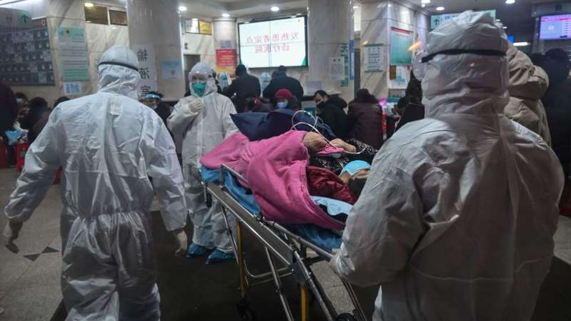a group of people standing around a bag of luggage: Medical staff wear protective clothing with a patient at the Wuhan Red Cross Hospital