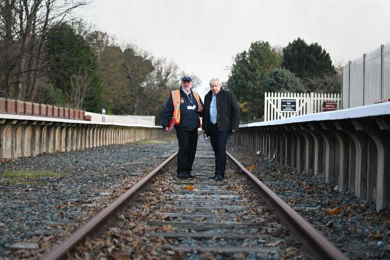 a man standing on a train track near a fence: Boris Johnson last year during a visit to Thornton-Cleveleys Railway Station, on the disused Fleetwood and Poulton-le-Fylde line while General Election campaigning.