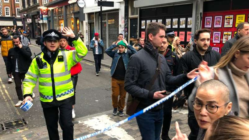 a group of people standing in front of a crowd: Police leave a cordoned off area in Soho on Monday.
