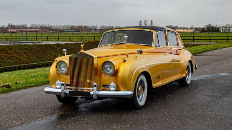 a yellow car parked on the side of a road: Artcurial George Barris Custom Rolls Royce