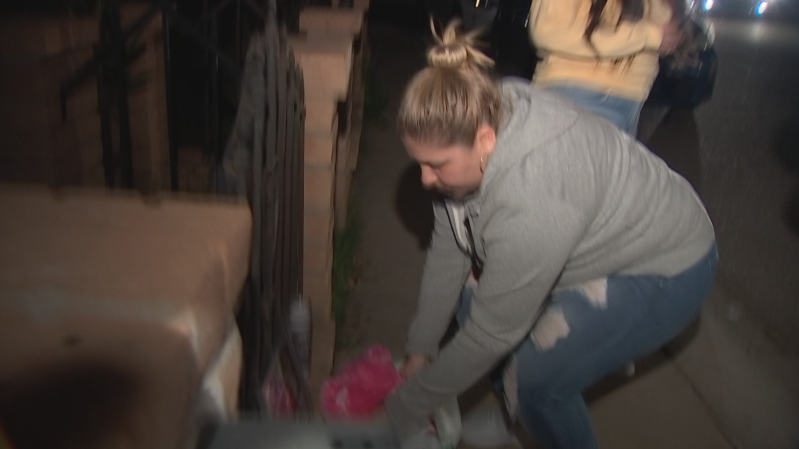 a man standing in a room: A woman claiming to be the biological mother of the young girl whose skeletal remains were found in a burned Phoenix home last week lays flowers down at the girl's memorial.