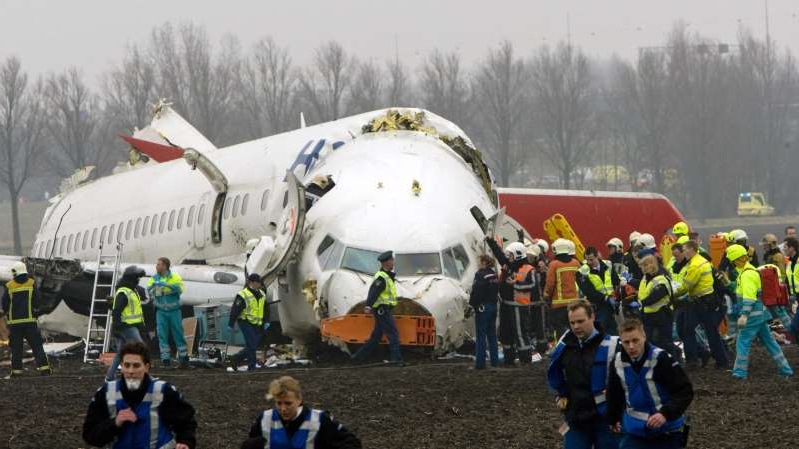 a group of people standing around a plane: Dutch lawmakers are reviewing an investigation into a deadly crash near Amsterdam in 2009.