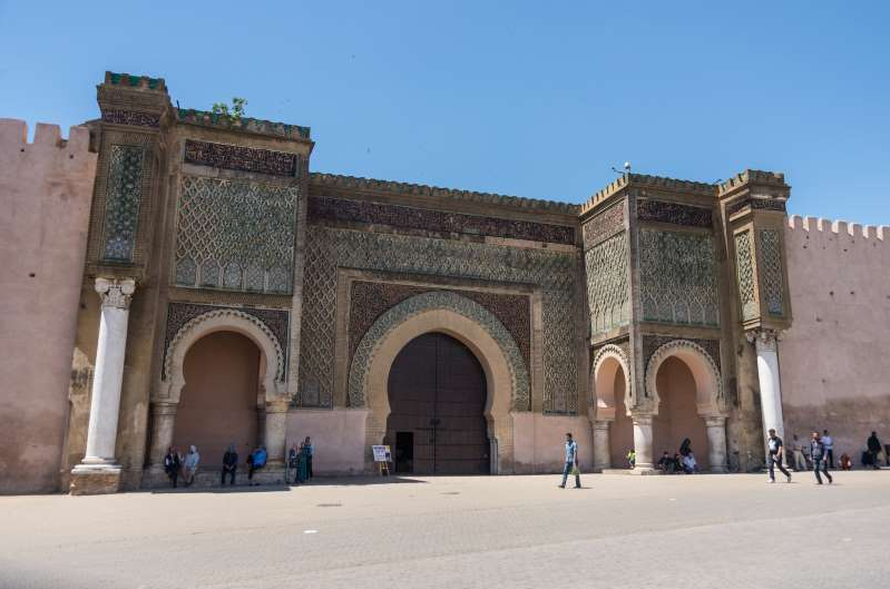 a large stone statue in front of Meknes: A record 13 million tourists visited Morocco in 2019, up 5.2 percent from the previous year.