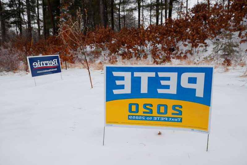 Campaign signs for Democratic presidential candidates Pete Buttigieg and Bernie Sanders stand in the snow in Manchester, New Hampshire, on February 7, 2020.