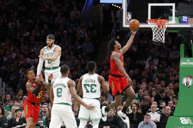 a basketball player in front of a crowd: Atlanta Hawks guard Treveon Graham drives to the basket ahead of Boston Celtics defenders during the first half of an NBA basketball game, Friday, Feb. 7, 2020, in Boston. (AP Photo/Mary Schwalm)