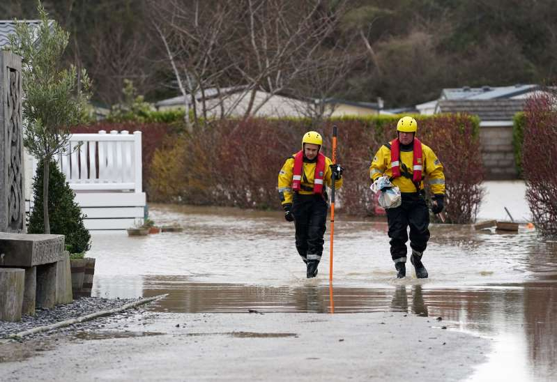 Fire service personnel wade though a flooded street in St. Asaph in North Wales.