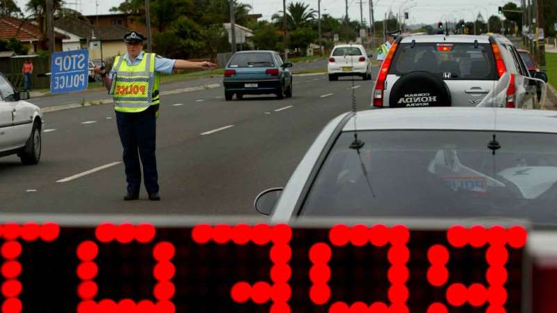 a person driving a car: A roadside random breath test.