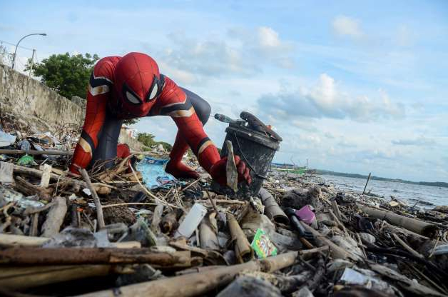 a pile of hay: Rudi Hartono, a man dressed in Spiderman costume, collects rubbish at a beach in Pare-Pare
