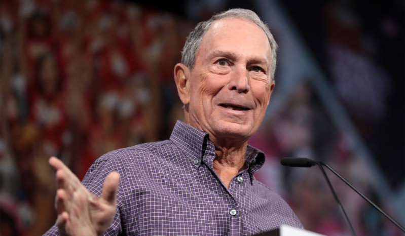 Michael Bloomberg holding a microphone: Mike Bloomberg speaks at the Presidential Gun Sense Forum in Des Moines, Iowa, August 10, 2019.