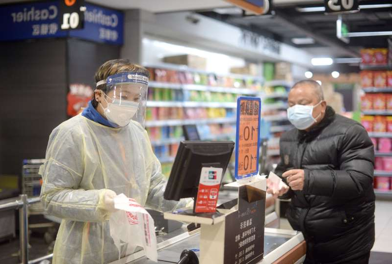 WUHAN, CHINA - FEBRUARY 10 2020: A cashier in a plastic gown works at the checkout of a supermarket in Wuhan, the epicenter of the novel coronavirus outbreak, in central China's Hubei province Monday, Feb. 10, 2020.- PHOTOGRAPH BY Feature China / Barcroft Media (Photo credit should read Feature China/Barcroft Media via Getty Images)