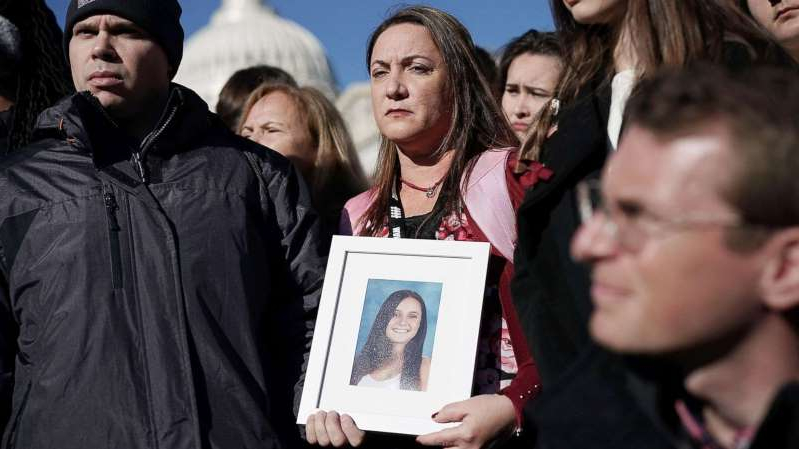 a group of people posing for the camera: Lori Alhadeff and her husband Ilan Alhadeff right, hold a picture of their daughter Alyssa Alhadeff, a Marjory Stoneman Douglas High School shooting victim, during a news conference on gun control in Washington, D.C., March 23, 2018.