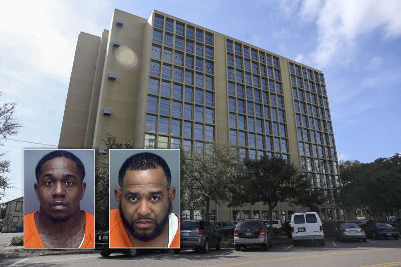 a person standing in front of a building: Ahmad Weston, left, and Charleston Long are awaiting trial in federal court. They are accused of running a drug ring out of their mother's apartment in a downtown St. Pete senior complex.