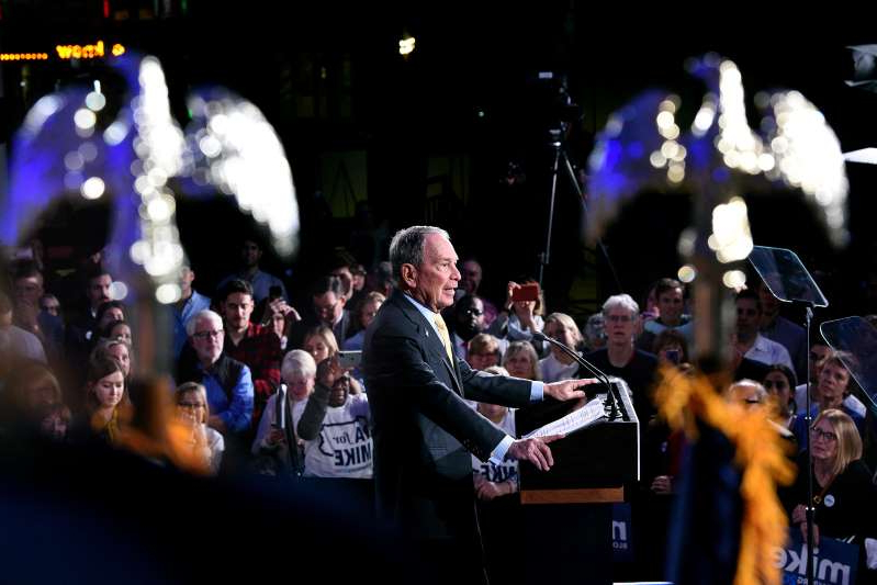 Michael Bloomberg standing on a stage with a crowd watching: Democratic presidential candidate Mike Bloomberg appears at a campaign rally at the National Constitution Center on Tuesday, Feb. 4, 2020.
