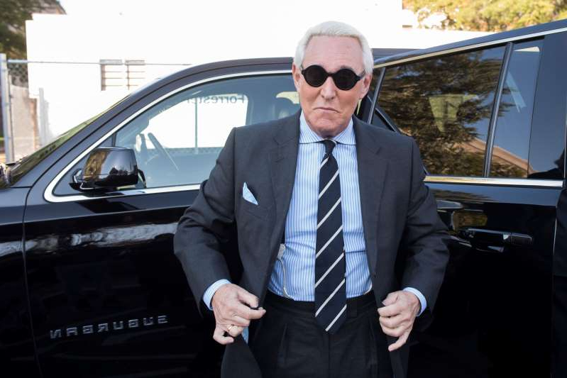 Roger Stone wearing a suit and tie standing next to a car: Roger Stone arrives at federal court for the second day of jury selection for his federal trial in November 2019 in Washington.