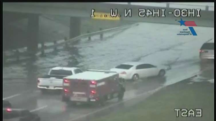 a car driving down a busy highway: Flooding at Interstate 30 and Interstate 45 conjunction