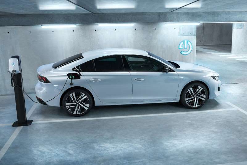 a car parked in a parking lot: Peugeot 508 plug-in hybrid - side view