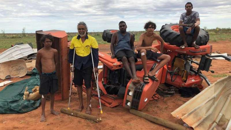 a group of people sitting at a beach: Bawoorrooga Community residents survey the damage from freak storm that struck the community on Tuesday evening. (Supplied: Foundation for Indigenous Sustainable Health)