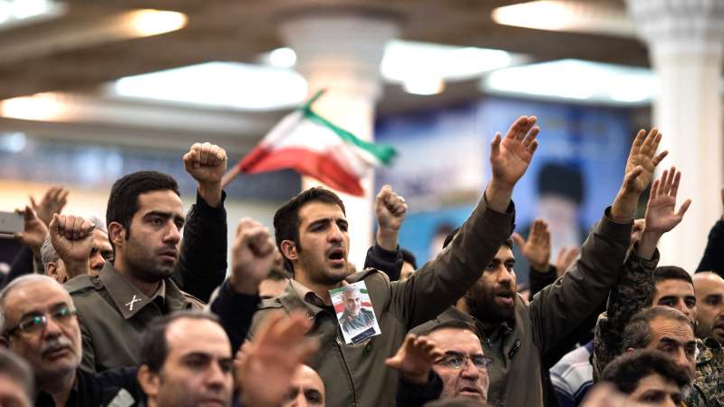a group of people standing in front of a crowd: The killing last month of the top Iranian military leader Qassim Suleimani escalated tensions with the United States, and in Iran, brought mourners into the streets.